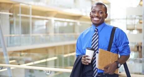 Portrait of a young businessman holding a warm beverage and business documents